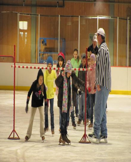 Image of children doing the limbo on skates during a field trip