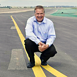 img of Mark Lovin Director of Aviation crouched on centerline of a runway smiling hands clasped in front